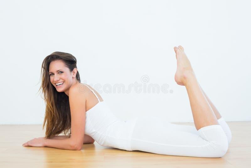 说谎在地板上的适合的妇女在健身演播室 图库摄影