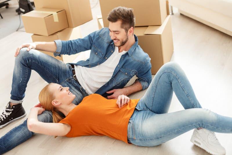 说谎在地板上的逗人喜爱的夫妇在他们新的家 免版税图库摄影