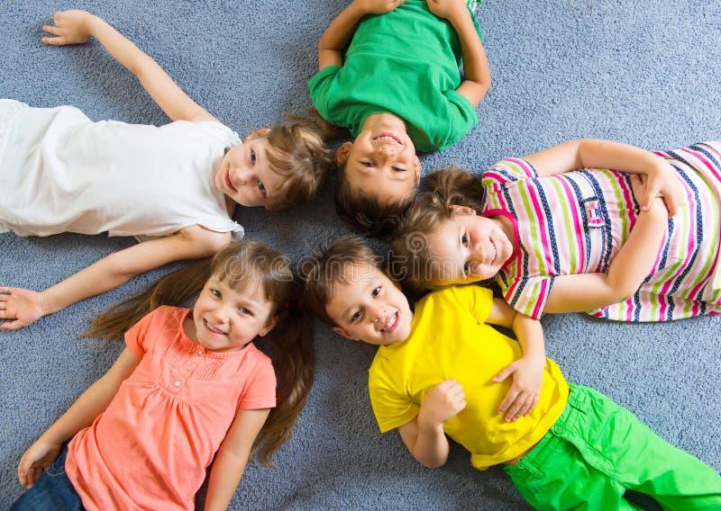 说谎在地板上的逗人喜爱的小孩 免版税图库摄影