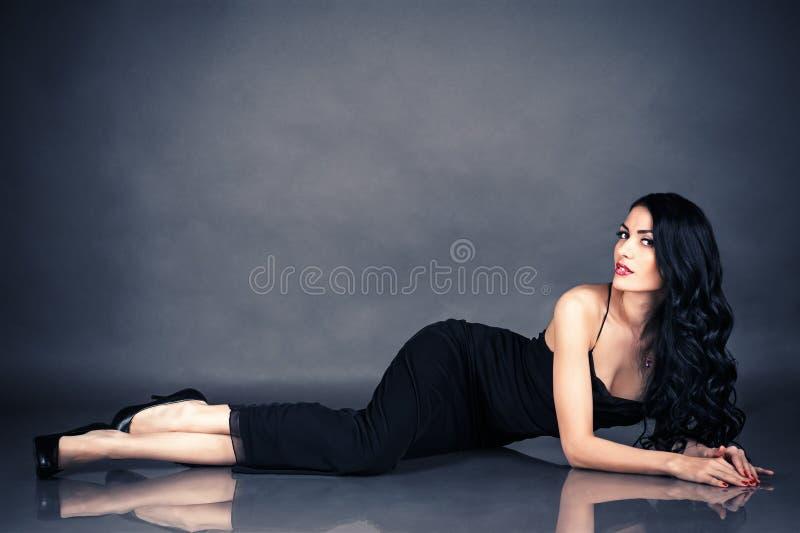 说谎在地板上的黑礼服的诱人的妇女 免版税库存照片