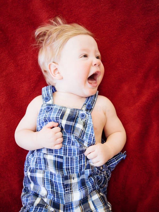 说谎在地板红色毯子的逗人喜爱的可爱的白种人微笑的男婴女孩画象在孩子屋子尖叫的哭泣里 免版税库存图片