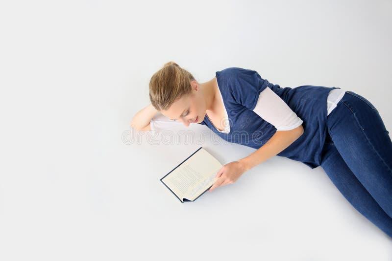 说谎在地板阅读书的少妇 图库摄影
