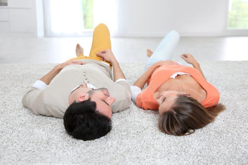 说谎在地毯地板上的夫妇 库存照片