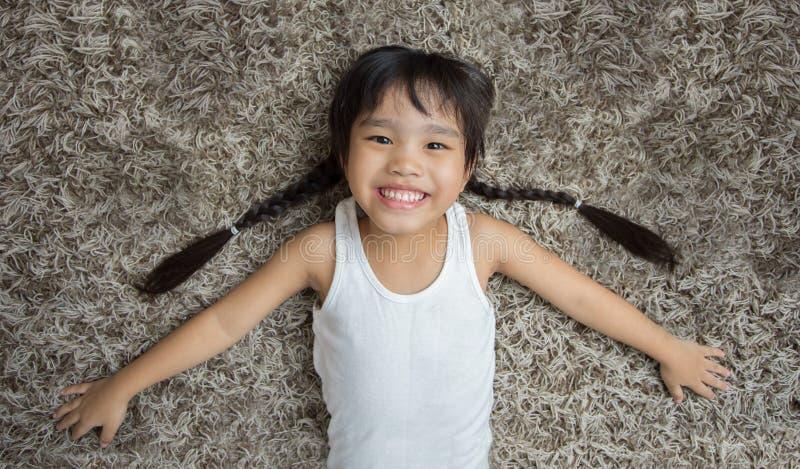说谎在地毯的微笑的逗人喜爱的小女孩 免版税库存照片