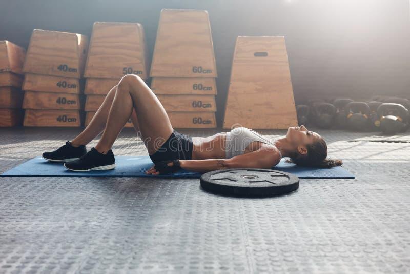 说谎在她的健身妇女在健身房锻炼以后 库存照片