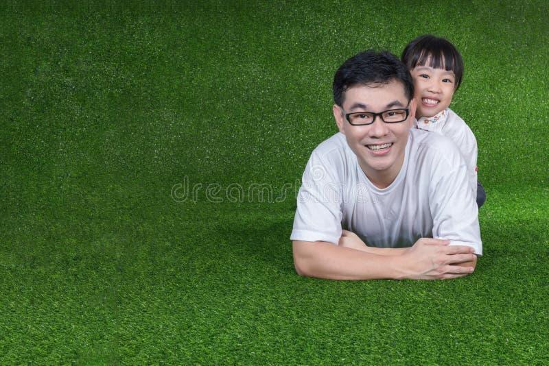 说谎在她的父亲` s后面的亚裔中国小女孩 免版税图库摄影