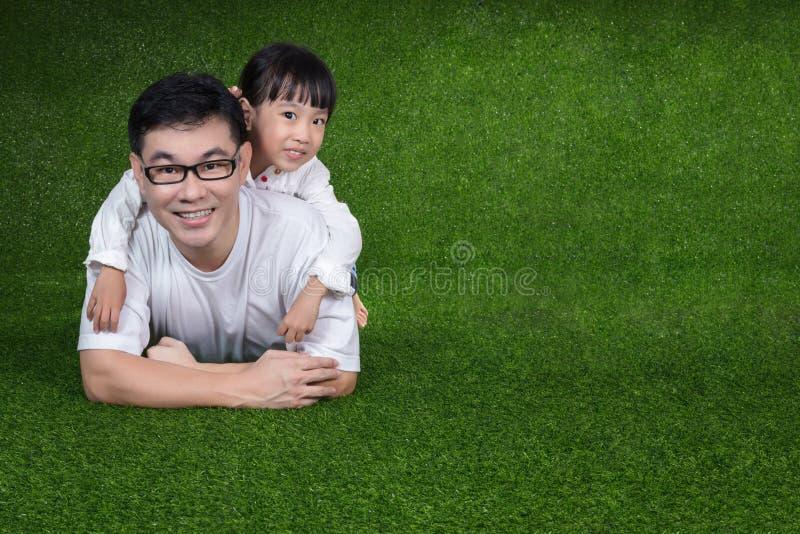 说谎在她的父亲` s后面的亚裔中国小女孩 免版税库存照片