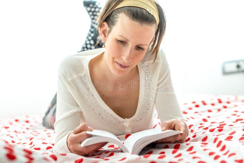 说谎在她的胃的妇女,当读书时 免版税库存图片