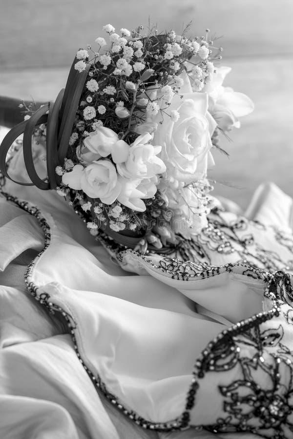 说谎在婚礼服的美丽的婚礼花束 免版税库存图片