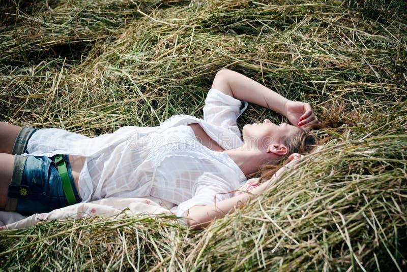 说谎在干草的年轻美丽的妇女的图片一个夏日 库存图片
