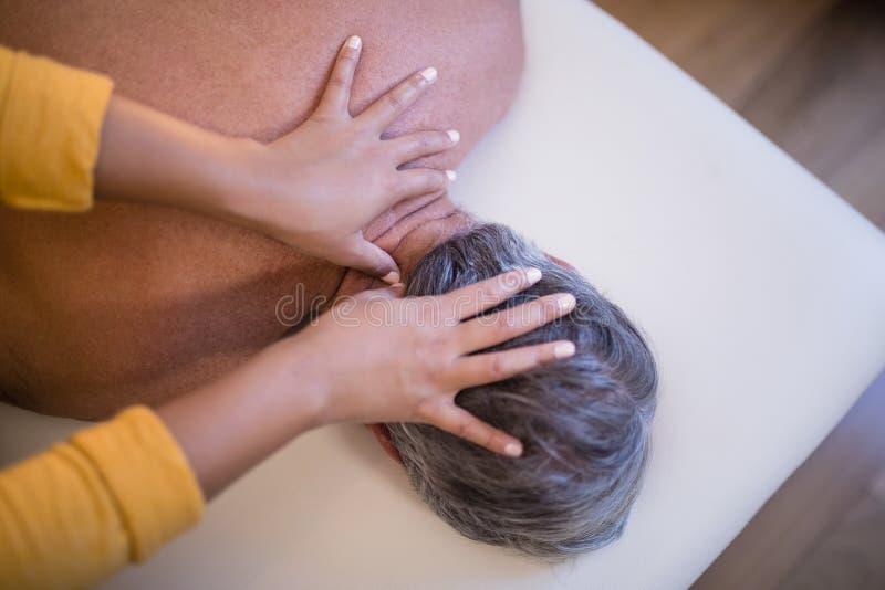 说谎在床上的赤裸上身的资深男性患者背面图接受脖子按摩从女性治疗师 免版税库存图片