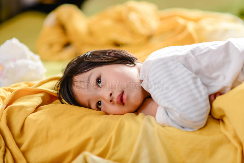 说谎在床上的逗人喜爱的亚裔孩子 免版税库存照片