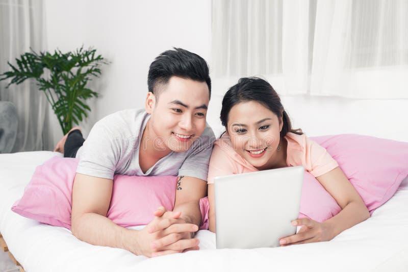 说谎在床上的年轻亚洲夫妇使用数字式片剂 免版税库存图片