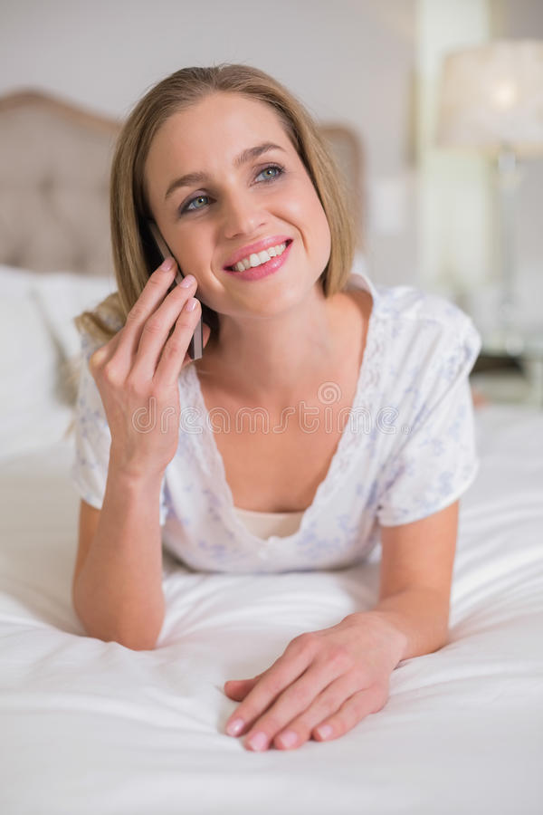 说谎在床打电话的自然笑的妇女 免版税库存图片