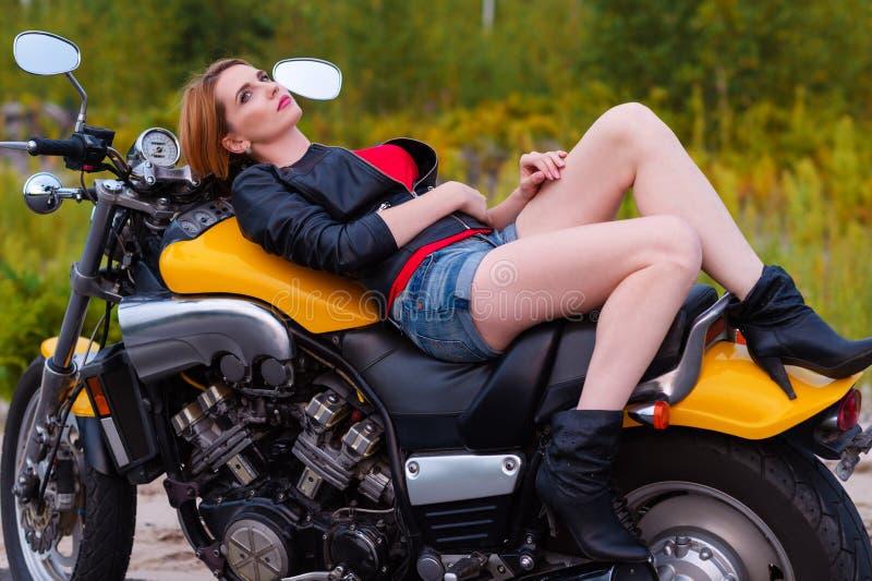 说谎在摩托车的性感的年轻骑自行车的人妇女 免版税库存图片
