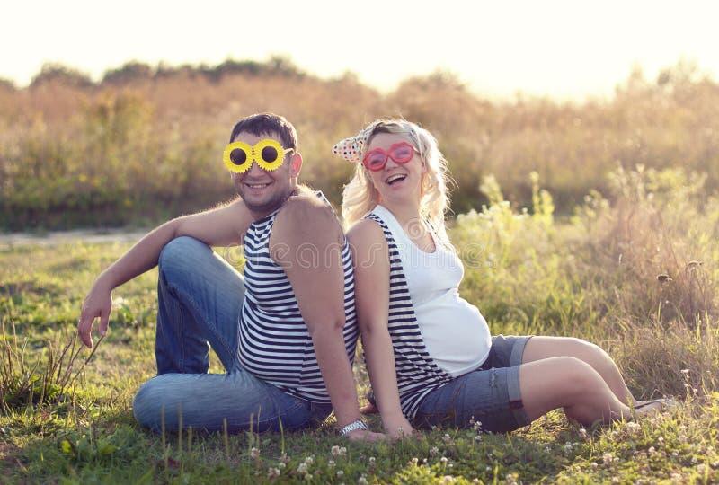 说谎在有她的丈夫的草坪的年轻美丽的夫人 免版税库存照片