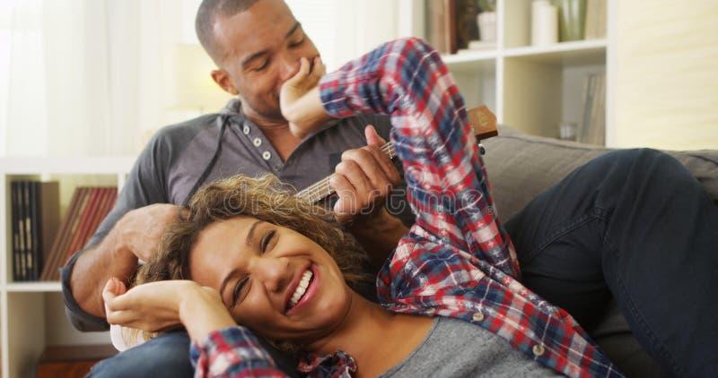 说谎在有尤克里里琴的长沙发的愉快的黑夫妇 库存图片