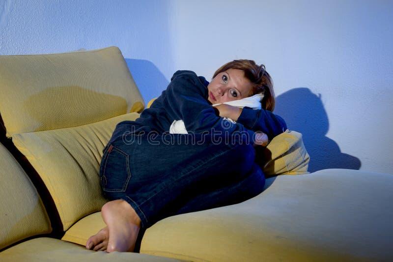 说谎在有枕头坐垫的长沙发的妇女在重音和消沉 免版税图库摄影