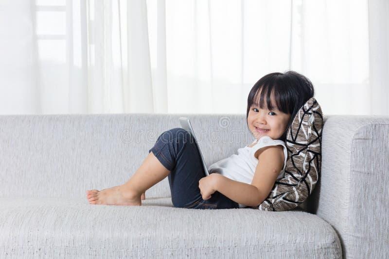 说谎在有片剂的沙发的愉快的亚裔中国小女孩 库存照片