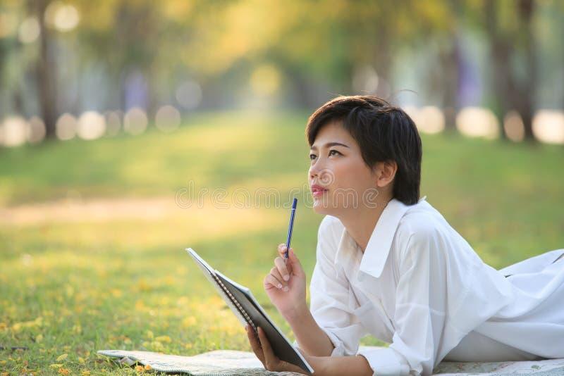 说谎在有铅笔和笔记本的绿草公园的少妇 库存照片