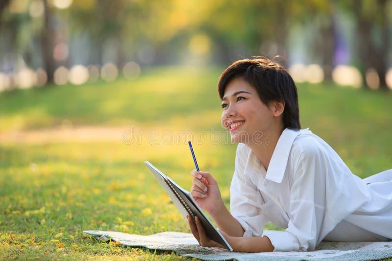 说谎在有铅笔和笔记本的绿草公园的少妇 库存图片