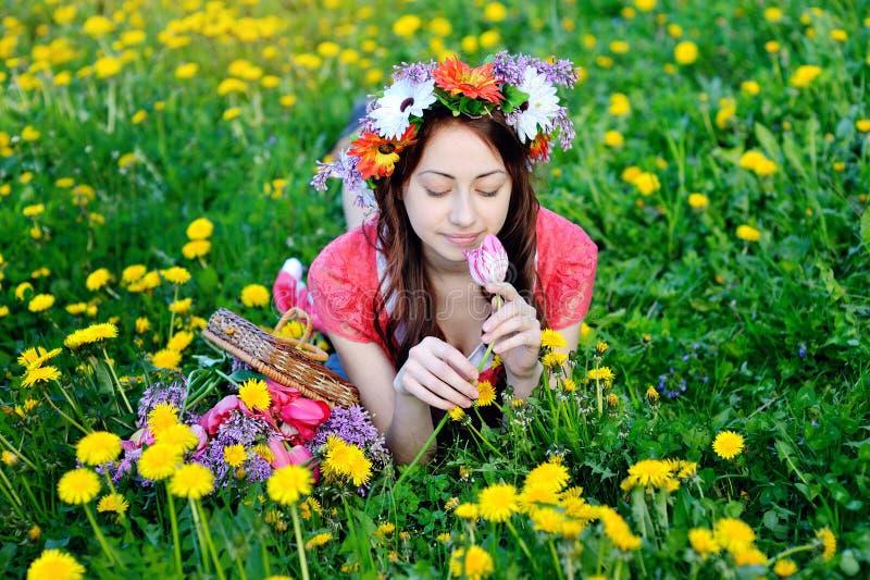 说谎在有黄色花的草甸的一件红色礼服的美丽的妇女 图库摄影
