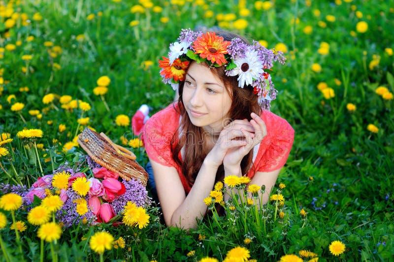 说谎在有黄色花的草甸的一件红色礼服的美丽的妇女 免版税库存照片