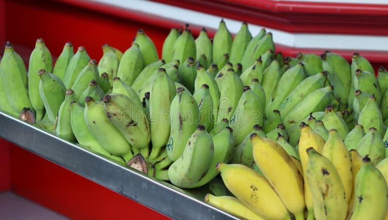 说谎在柜台的束绿色和黄色香蕉待售 免版税库存图片