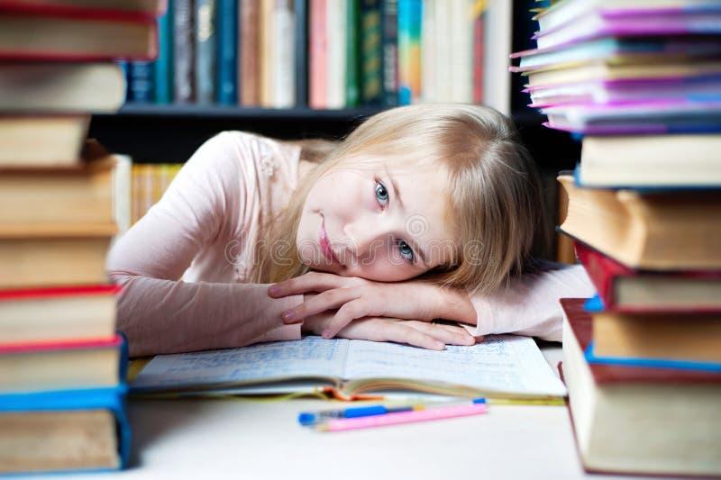 说谎在桌上的逗人喜爱的小女孩,当做她的家庭作业时 图库摄影
