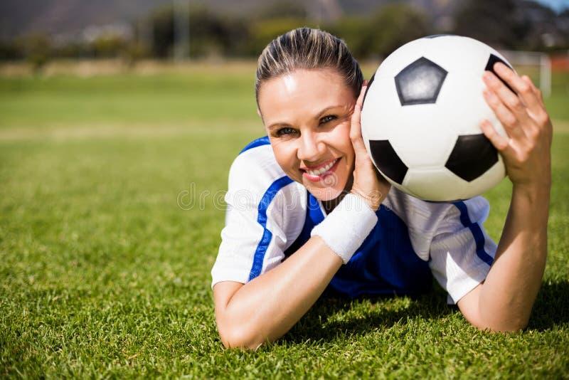 说谎在橄榄球场和拿着球的女性足球运动员画象  免版税库存照片