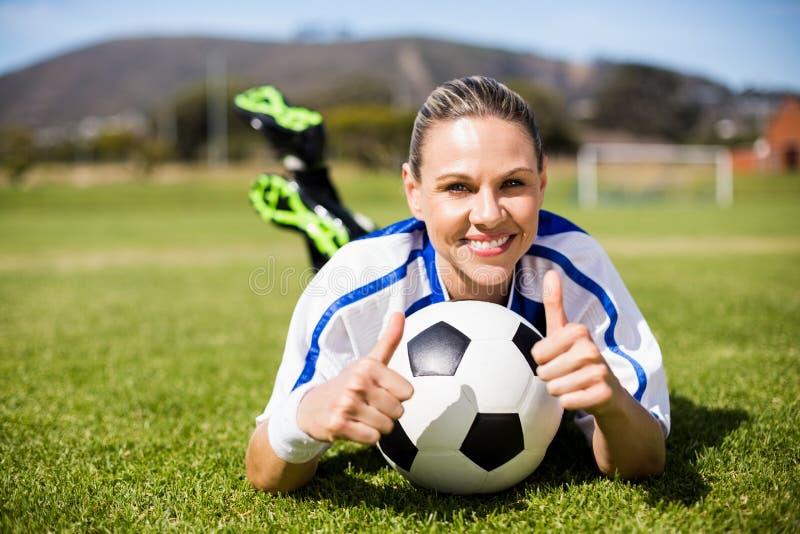 说谎在橄榄球场和显示她的拇指的女性足球运动员画象  库存照片