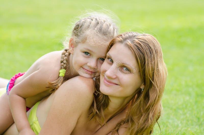 说谎在母亲的女儿愉快地拥抱她,以绿草为背景 免版税库存照片