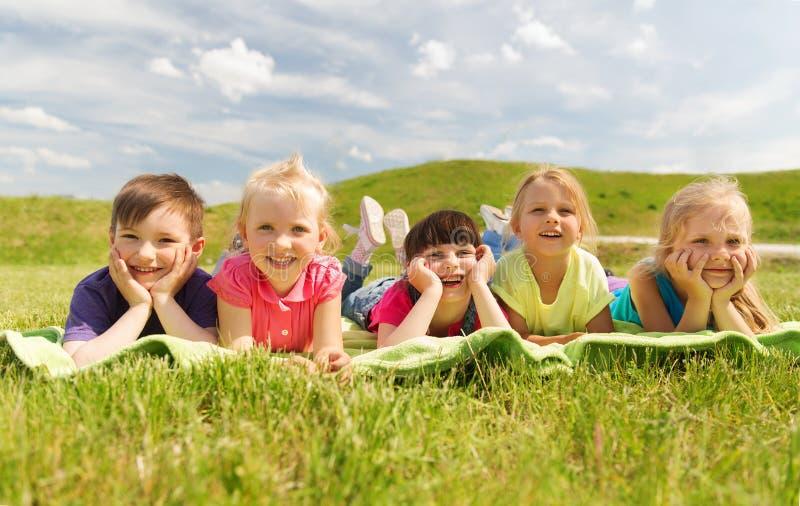 说谎在毯子或盖子的小组孩子户外 库存图片