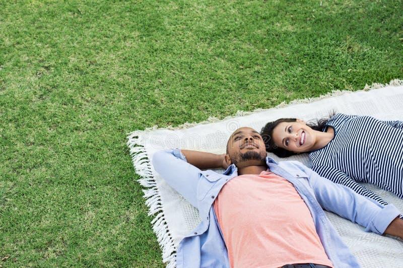 说谎在毯子的夫妇在公园 免版税库存照片