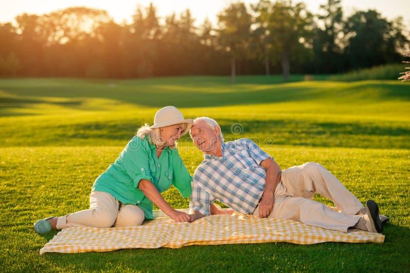 说谎在毯子的年长夫妇 库存照片