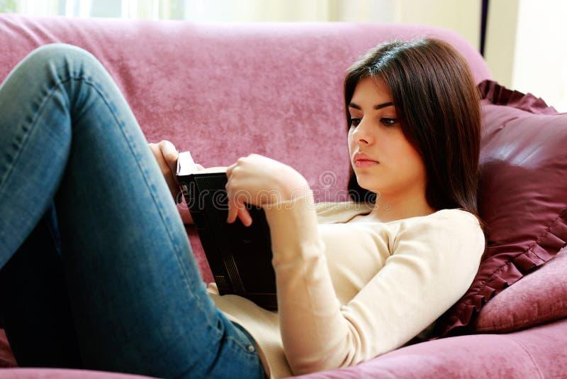 说谎在沙发和阅读书的年轻美丽的妇女 免版税库存图片