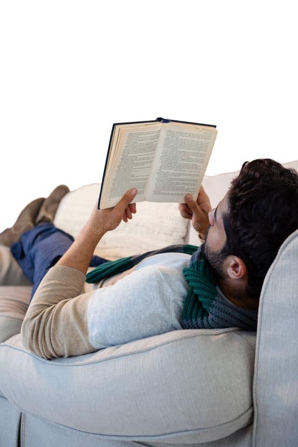 说谎在沙发的人,当阅读书时 免版税库存图片