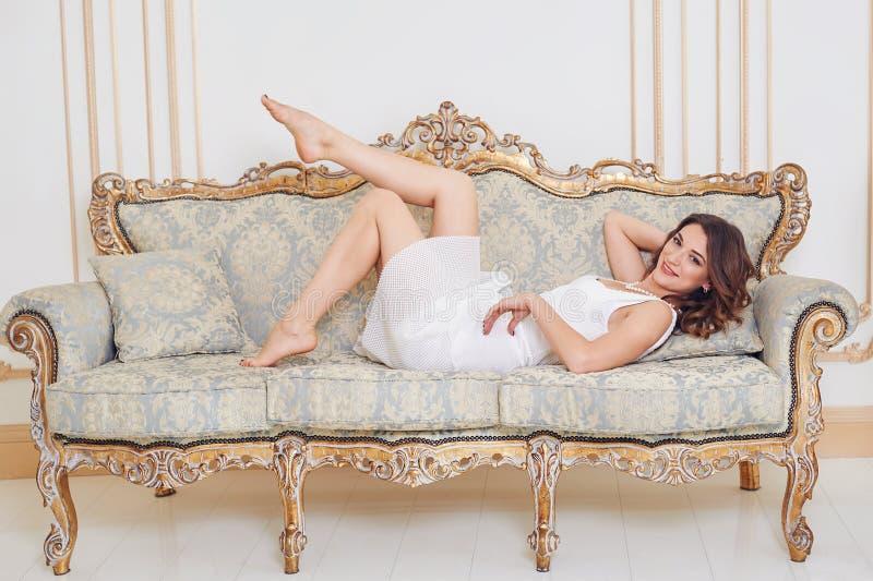 说谎在沙发的华美的美丽的少妇 库存照片