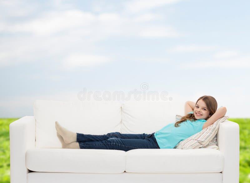 说谎在沙发的微笑的小女孩 免版税库存图片