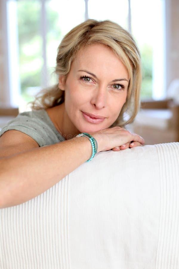 说谎在沙发的成熟妇女画象 免版税库存图片