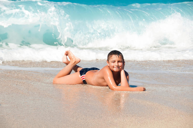 说谎在沙子和波浪的海的男孩 免版税库存照片