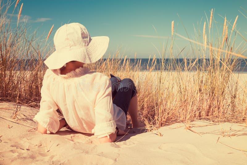 说谎在沙子和看海的帽子的夫人 库存图片