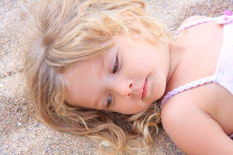 说谎在沙子的小女孩 免版税库存图片