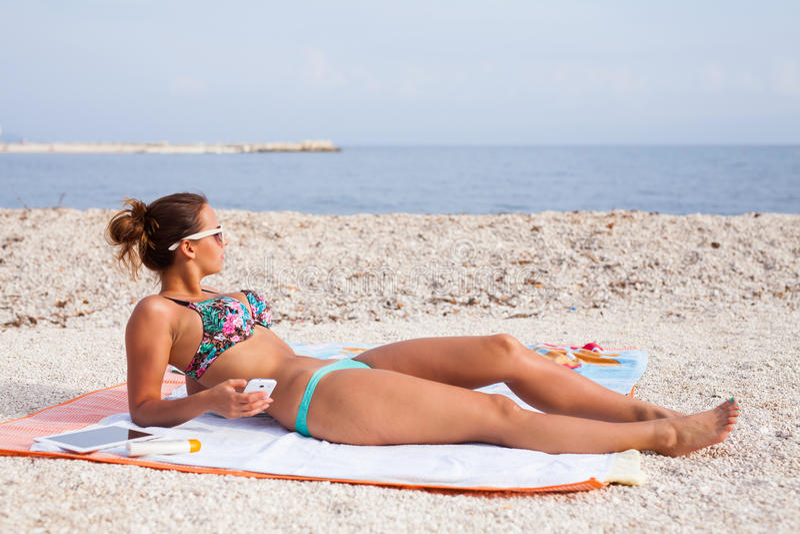 说谎在海滩和晒日光浴与在她的电话的俏丽的女孩 免版税图库摄影