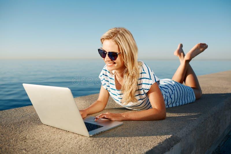 说谎在海滩的夏天在海附近和谈话的快乐的女孩 库存图片