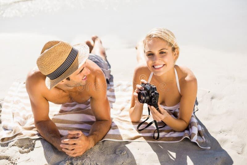 说谎在海滩的年轻夫妇 库存图片