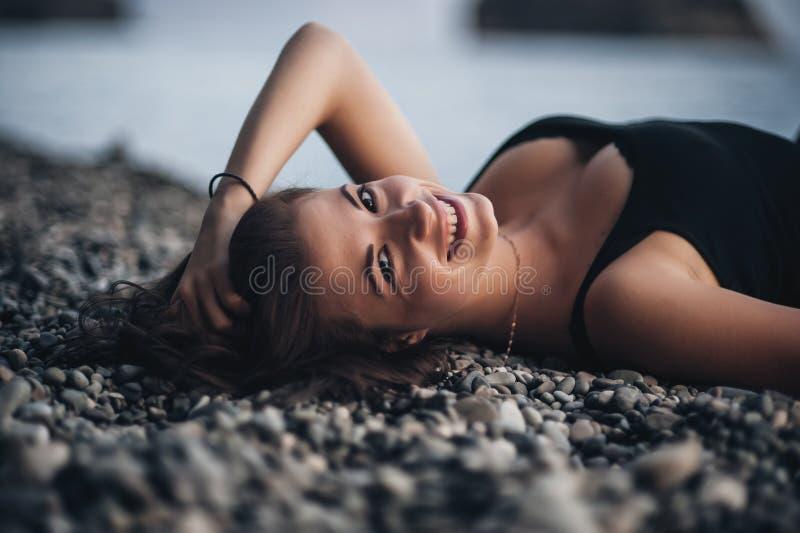 说谎在海滩的黑紧身礼服的性感的少妇在水中 免版税库存照片