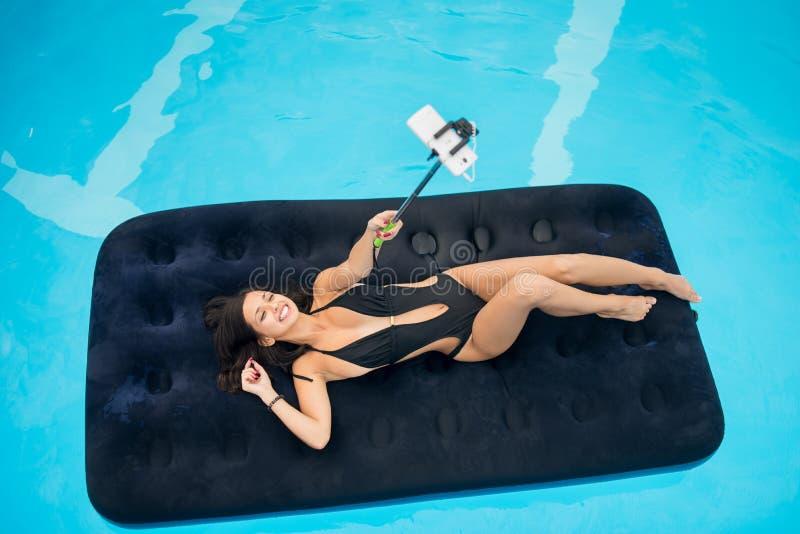说谎在游泳池的一个可膨胀的床垫的微笑的妇女和在电话做selfie照片用selfie棍子 库存照片