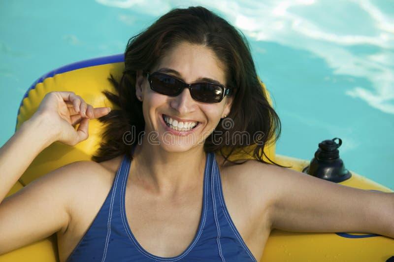 说谎在游泳池画象的可膨胀的木筏的妇女佩带的太阳镜。 免版税库存图片