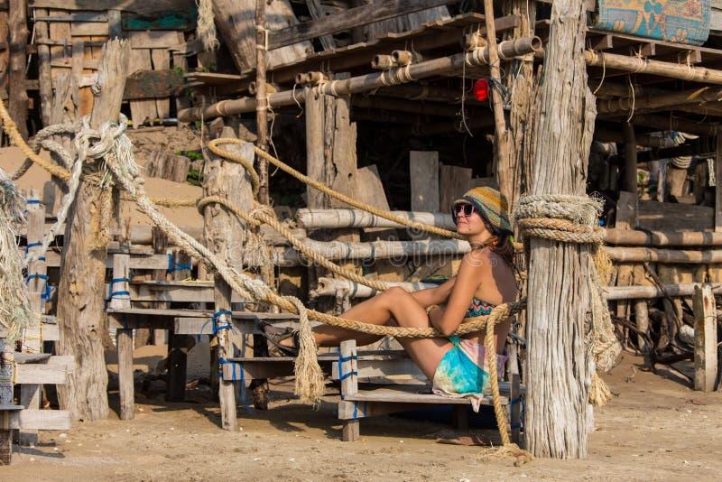 说谎在热带海滩的黄色比基尼泳装的妇女在塞舌尔群岛 免版税库存照片